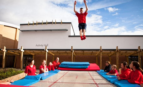 boy trampolining in courtyard